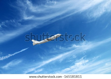 airplane flying on light cloudy background. - stock photo