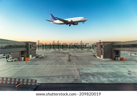 Airplane flying over airport - stock photo