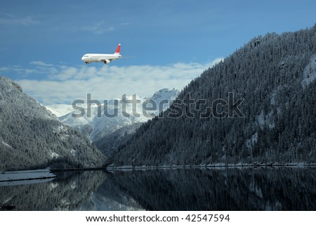 airplane flying over beautiful mountain's lake