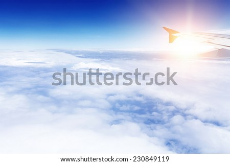airplane flying over clouds with wing in sunlight - stock photo