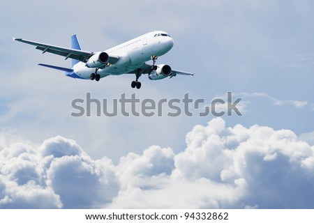 Airplane flying over cloudy sky. Commercial travel airline concept - stock photo