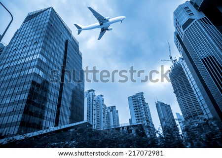 airplane flying over high buildings in modern city - stock photo