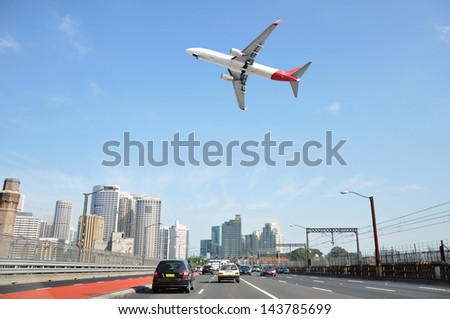 Airplane flying over the city - stock photo
