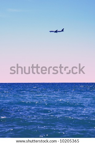 Airplane flying over the ocean. An overseas flight. - stock photo