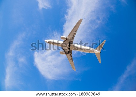 Airplane flying overhead with blue sky and the bottom of the airplane as it comes in for a landing at San Diego Airport. - stock photo