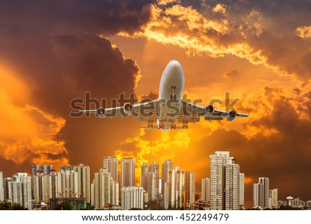 airplane flying take off from runway over modern skyscrapers on sunset background - stock photo