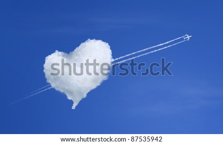Airplane flying through heart shaped cloud - stock photo