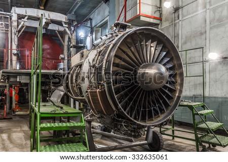 Airplane gas turbine engine detail in aviation hangar. Plane rotor under heavy maintenance. - stock photo
