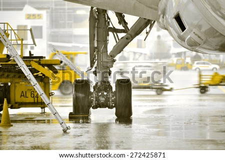 Airplane getting being service in heavy rain - stock photo