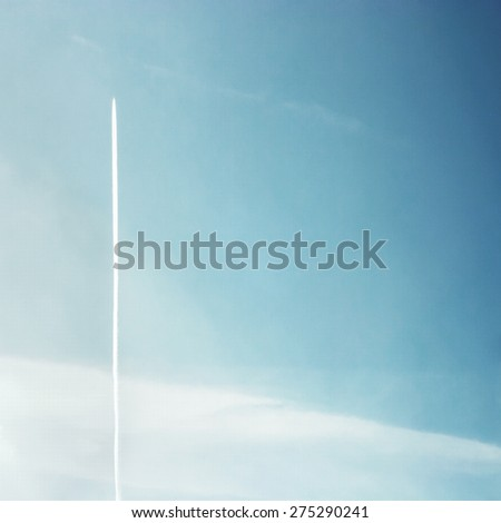 Airplane in Blue Sky with Condensation Trail background - stock photo