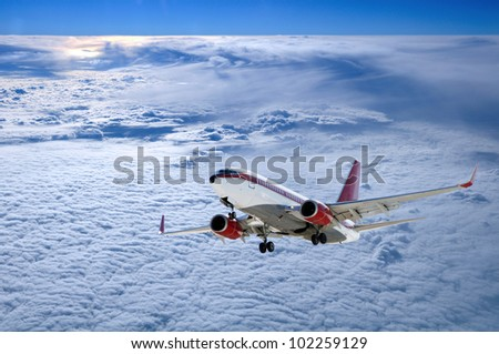 airplane in cloudscape with sunset above clouds - stock photo