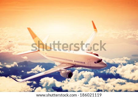 Airplane in flight. A big passenger or cargo aircraft, airline above clouds. Travel, transportation, transport, business in motion. - stock photo