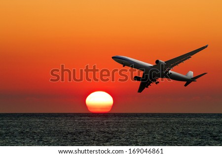 airplane in flight over ocean against beautiful sunset - stock photo