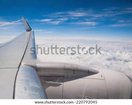 Airplane in flight, wing detail in a sunny day. - stock photo