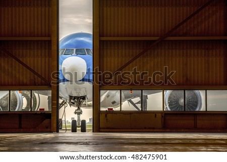 Airplane in front of half opened door to hangar