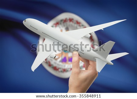 Airplane in hand with local US state flag on background - Virginia - stock photo