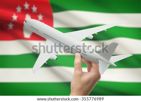 Airplane in hand with national flag on background - Abkhazia - stock photo
