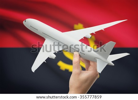 Airplane in hand with national flag on background - Angola - stock photo