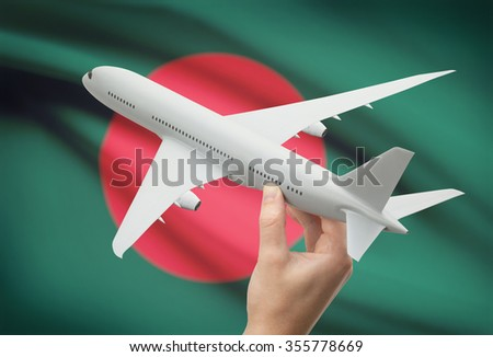 Airplane in hand with national flag on background - Bangladesh - stock photo