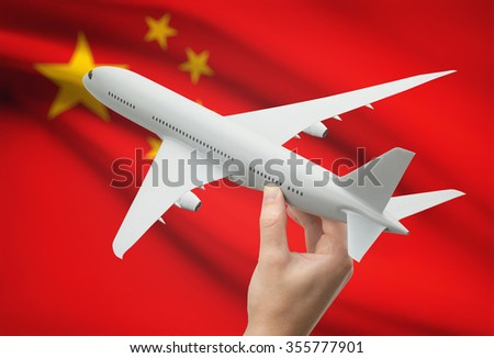 Airplane in hand with national flag on background - China - stock photo