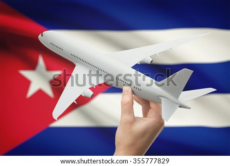 Airplane in hand with national flag on background - Cuba - stock photo