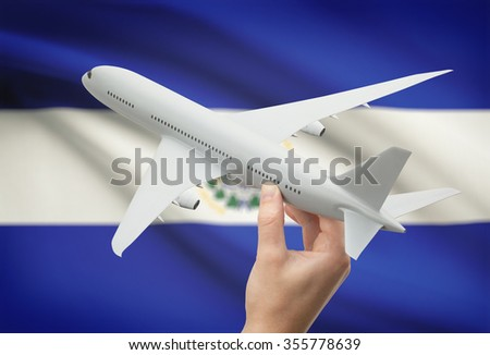 Airplane in hand with national flag on background - El Salvador - stock photo