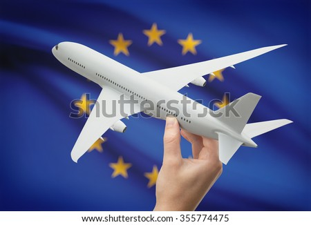 Airplane in hand with national flag on background - European Union - stock photo