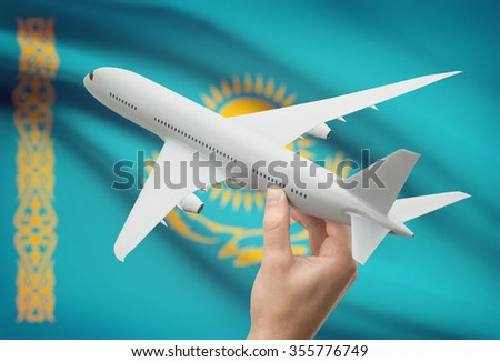 Airplane in hand with national flag on background - Kazakhstan - stock photo