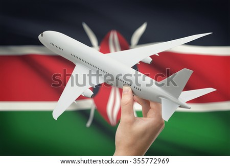 Airplane in hand with national flag on background - Kenya - stock photo
