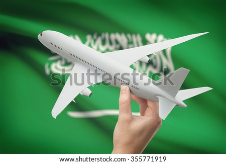 Airplane in hand with national flag on background - Saudi Arabia - stock photo