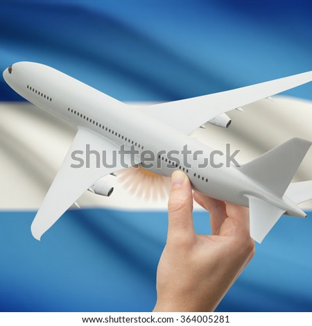 Airplane in hand with national flag on background series - Argentina - stock photo