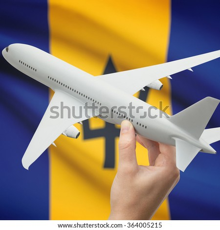 Airplane in hand with national flag on background series - Barbados - stock photo