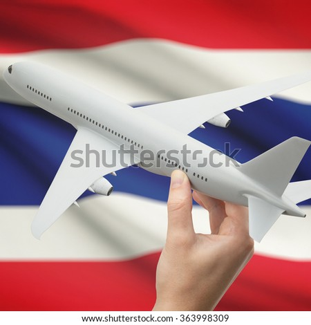 Airplane in hand with national flag on background series - Thailand - stock photo