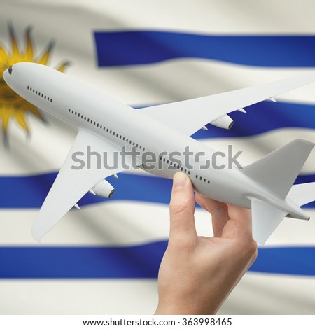 Airplane in hand with national flag on background series - Uruguay - stock photo
