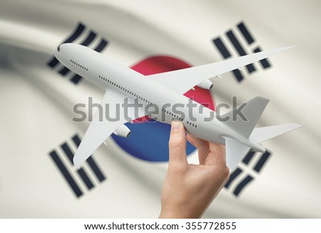 Airplane in hand with national flag on background - South Korea - stock photo