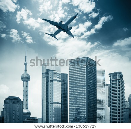 airplane in shanghai with modern buildings - stock photo