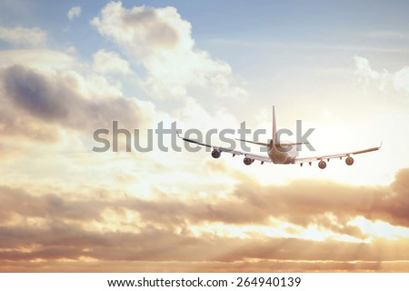 airplane in sunset sky - stock photo