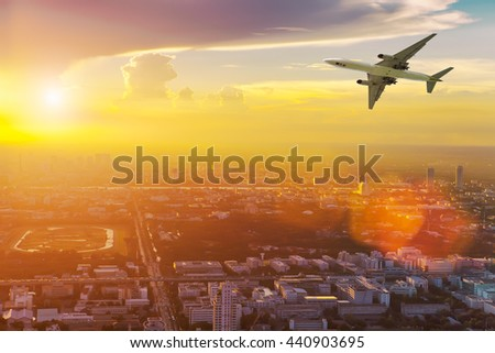 Airplane in the sky above city at sunset. Amazing trip. Travel concept. - stock photo
