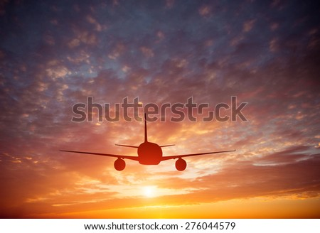 Airplane in the sky at a  beautiful sunset clouds - stock photo