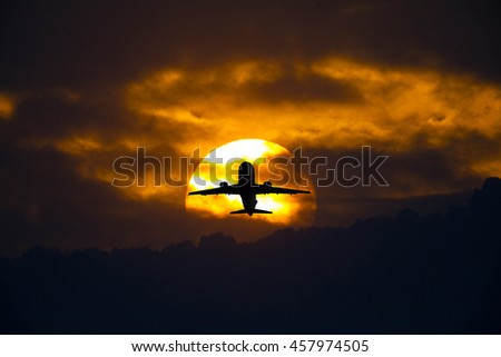 Airplane in the sky at sunrise - stock photo
