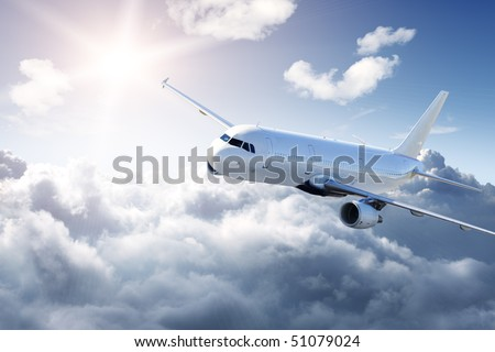 Airplane in the sky - cloudy but sunny day - stock photo