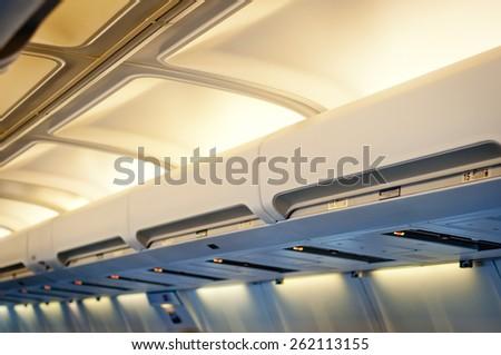 Airplane interior detail. Luggage shelf row. - stock photo