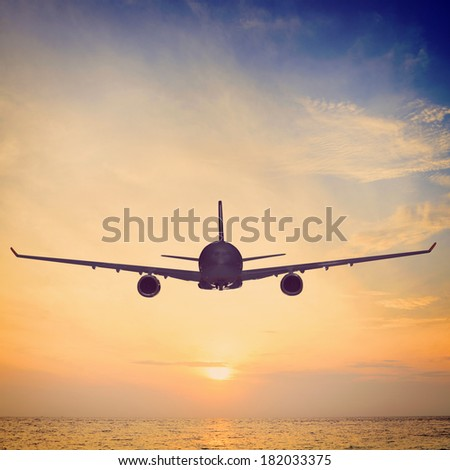 airplane is flying over the sea at sunset - stock photo