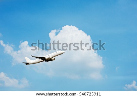 Airplane is flying past clouds in a blue sky