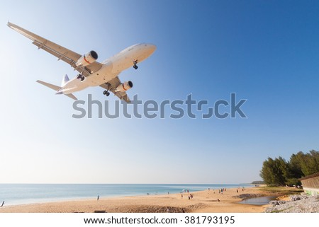 Airplane is landing at Phuket airport over the Mai Khao beach , Thailand - stock photo