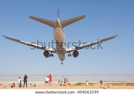 Airplane is landing at Phuket airport over the Mai Khao beach , Thailand - stock photo