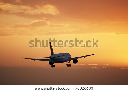 Airplane is landing at sunset, Prague Ruzyne Airport - stock photo