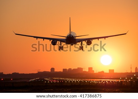 Airplane is landing at the airport during sunrise in the Netherlands. - stock photo