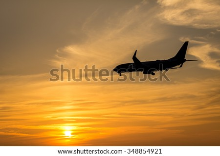 Airplane is landing at the runway during a beautiful sunset.