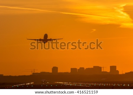 Airplane is taking off from the airport at dusk.